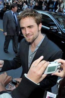 """Wenige Wochen vor dem Start von """"Breaking Dawn"""" schreibt Robert Pattinson in Paris fleißig Autogramme."""