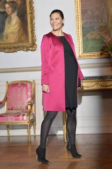 Bei einer Ausstellungseröffnung im Schloss in Stockholm bezaubert Prinzessin Victoria in einer Kombination aus schwarzem Kleid und pinkem Mantel.