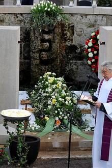Der Sarg wird in das von Mauern umgebene Grab gelassen.   Pfarrer Konrad Schreiegg hält die Trauerrede.