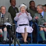 """1. September 2012: Da ist aber jemand """"very amused"""": Prinz Philip, Queen Elizabeth und Prinz Charles schauen fröhlich einem Sack"""
