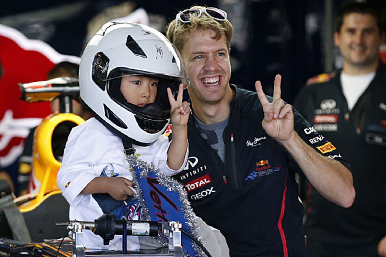 4. Oktober 2012: Victory! Vor dem Grand Prix in Suzuka nimmt sich Sebastian Vettel Zeit mit einem jungen Fan zu posieren.
