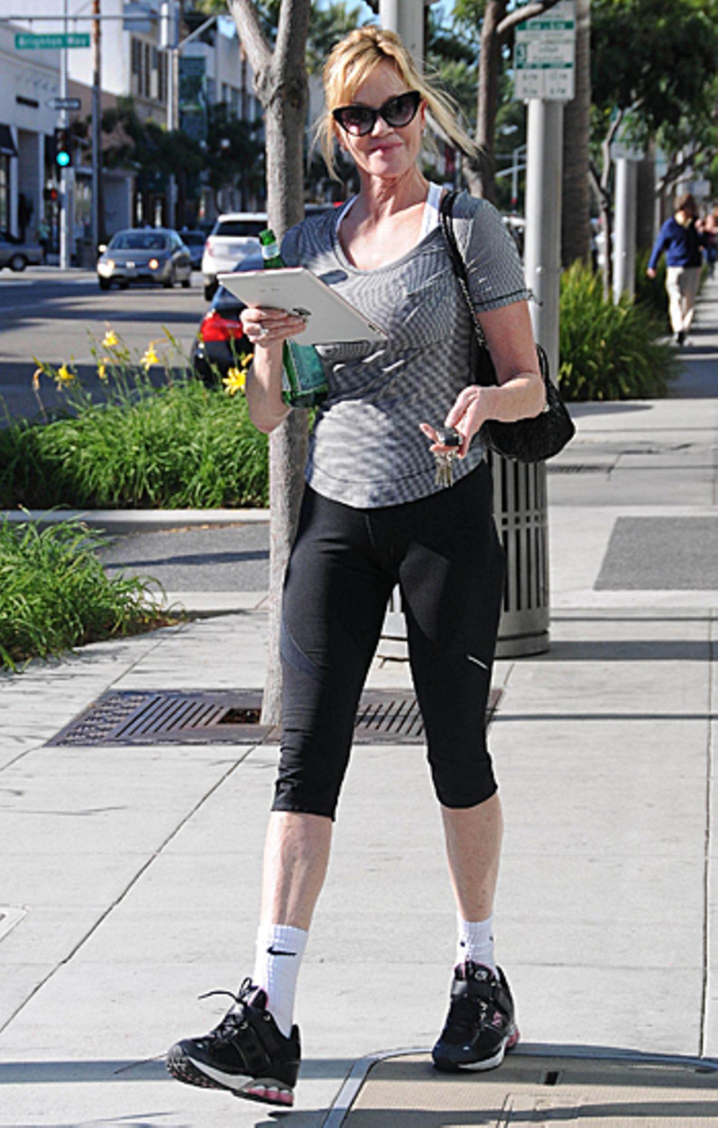 23. Oktober 2012: Sportlich und mobil unterwegs: Melanie Griffith spaziert in Trainingsklamotten und mit Ipad in der Hand durch