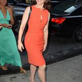 """Sex and the City""-Star Kristin Davis in einem orangefarbenen Kleid mit goldenem Zipper und schwarzen Keilabsatzschuhen - beides"