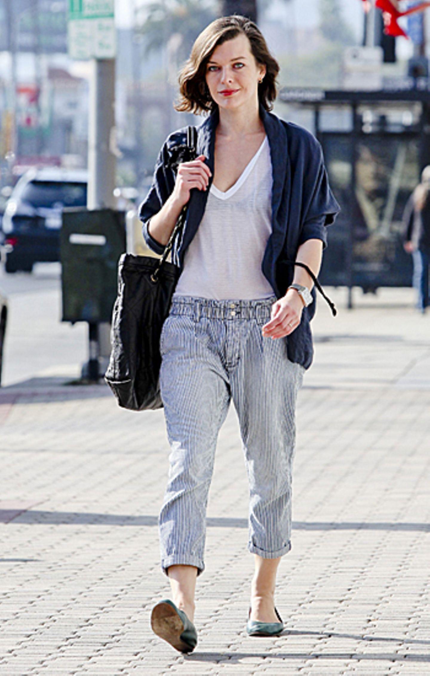 Milla Jovovich kann mit lockerer 7/8-Hose und transparentem Shirt die warmen Sonnenstrahlen in Hollywood genießen.