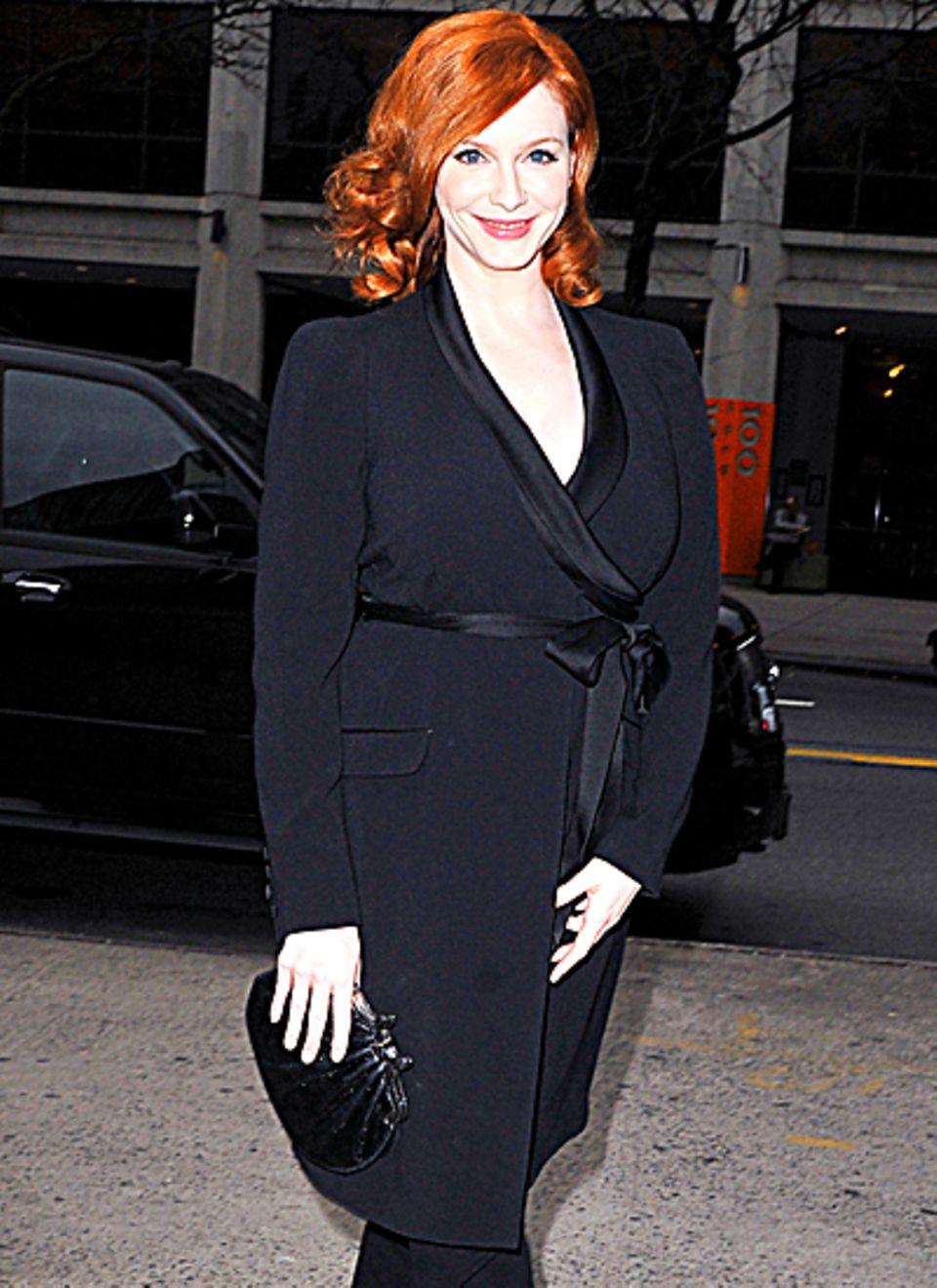 Der leichte Mantel in Schwarz bringt die Haare von Christina Hendricks noch mehr zum leuchten.