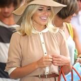 Mollie King ganz ladylike mit Hut und Kleid.
