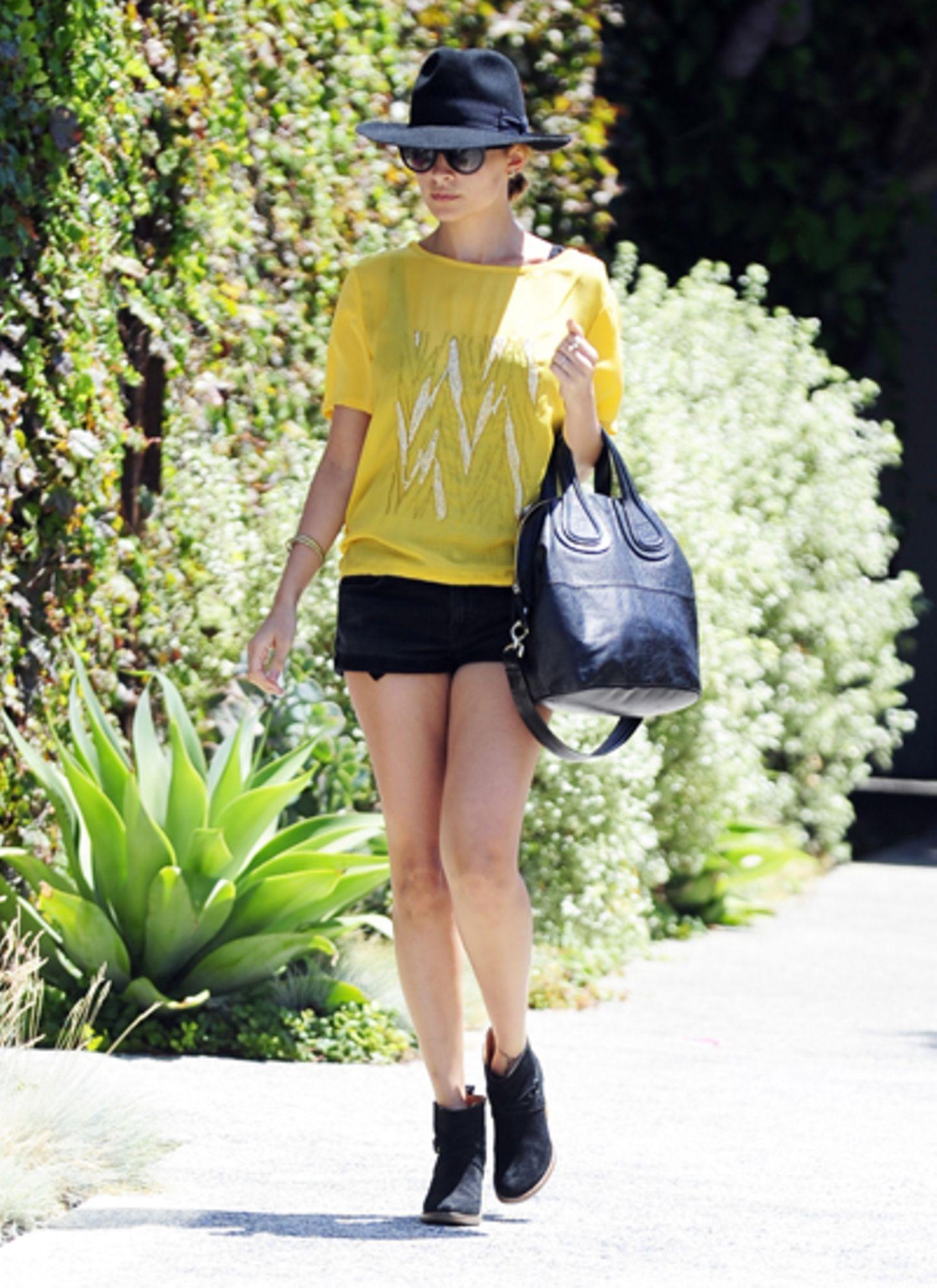 In Kombination mit Schwarz wirkt das gelbe Shirt von Nicole Richie ganz besonders anziehend. Auch sie ist ein Fan von knappen Hö