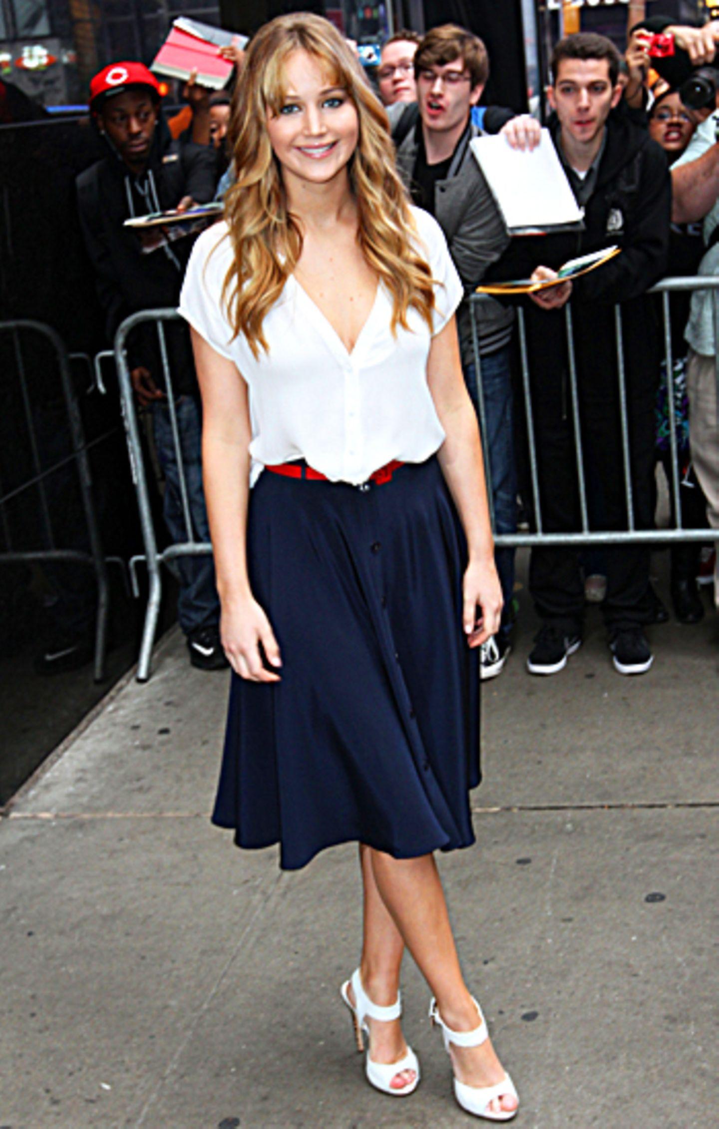Jennifer Lawrence in einem Rock von Holmes & Yang. Dazu trägt sie weiße Sandalen von Giuseppe Zanotti.