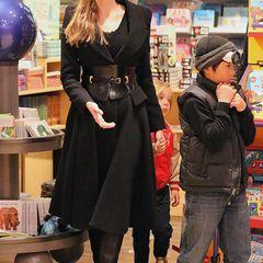 Ihren schwarzen Wollmantel kombiniert Angelina mit einem breiten Taillengürtel und Louboutin-Stiefeln.