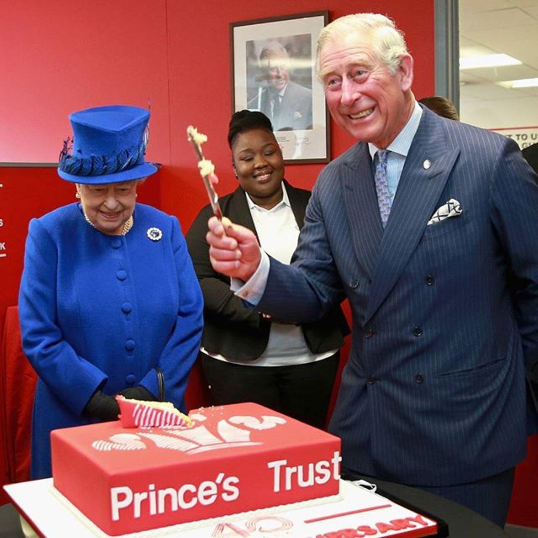 """Die Queen ist mit Prinz Charles auf dem 40. Geburtstag von """"Prince's Trust"""". Charles schneidet mit Freude die Torte an."""
