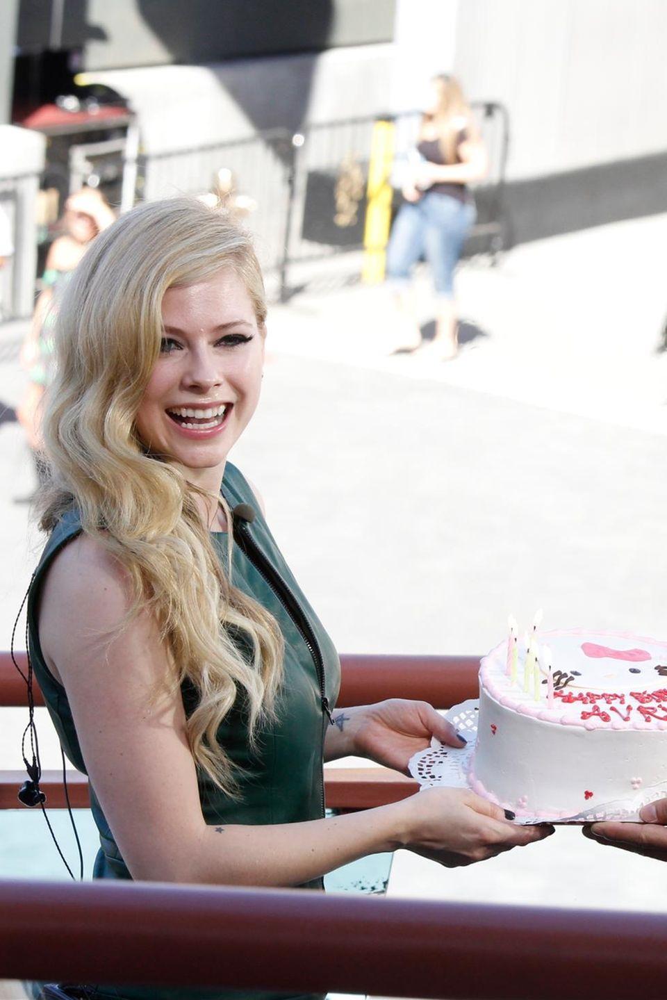 """Avril Lavigne bekommt zu ihrem Geburtstag eine Torte von """"Extra!""""-Moderator Mario Lopez."""