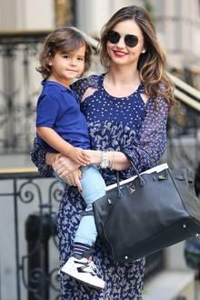Auf Mama Mirandas Arm ist es doch am schönsten. Obwohl Flynns weiße Sneaker zum Polohemd-Outfit zum Laufen sicher sehr bequem sind.