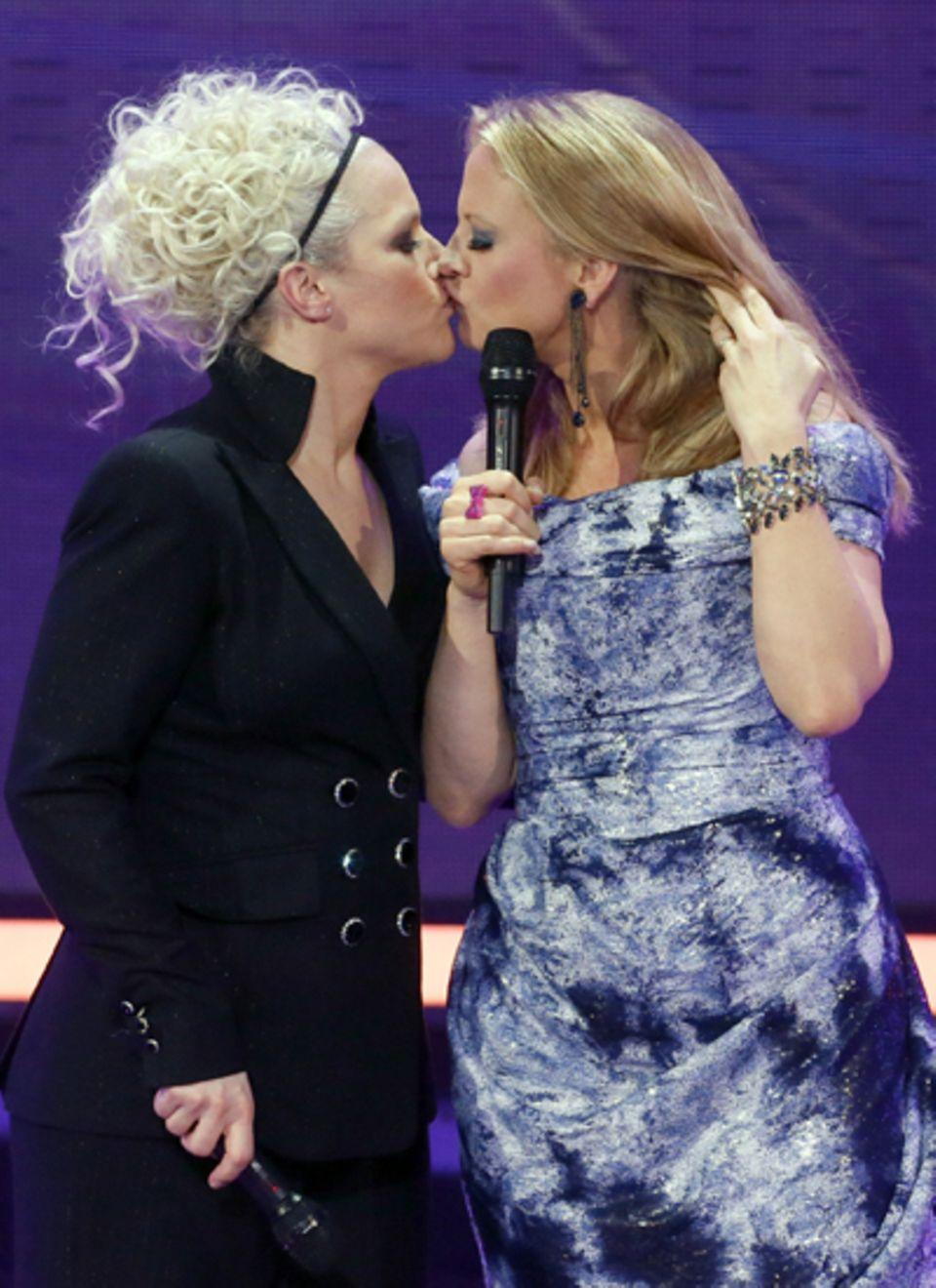 Das Moderatorengespann Ina Müller und Barbara Schöneberger sorgen mit ihrem Kuss für einen Hingucker-Moment und erinnern damit a