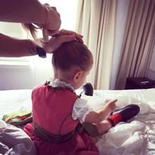 Papa ist der beste Friseur! Im süßen Dirndl sitzt Töchterchen Amelia auf dem Bett und lässt sich von Rocco geduldig frisieren.