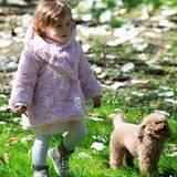 Auch wenn der Frühling in Mailand Einzug hält, mit ihrem rosafarbenen Kuschel-Mäntelchen und hohen beige-khakifarbenen Sneakern ist Sole Trussardi beim Spielen im Park noch schön warm eingepackt.