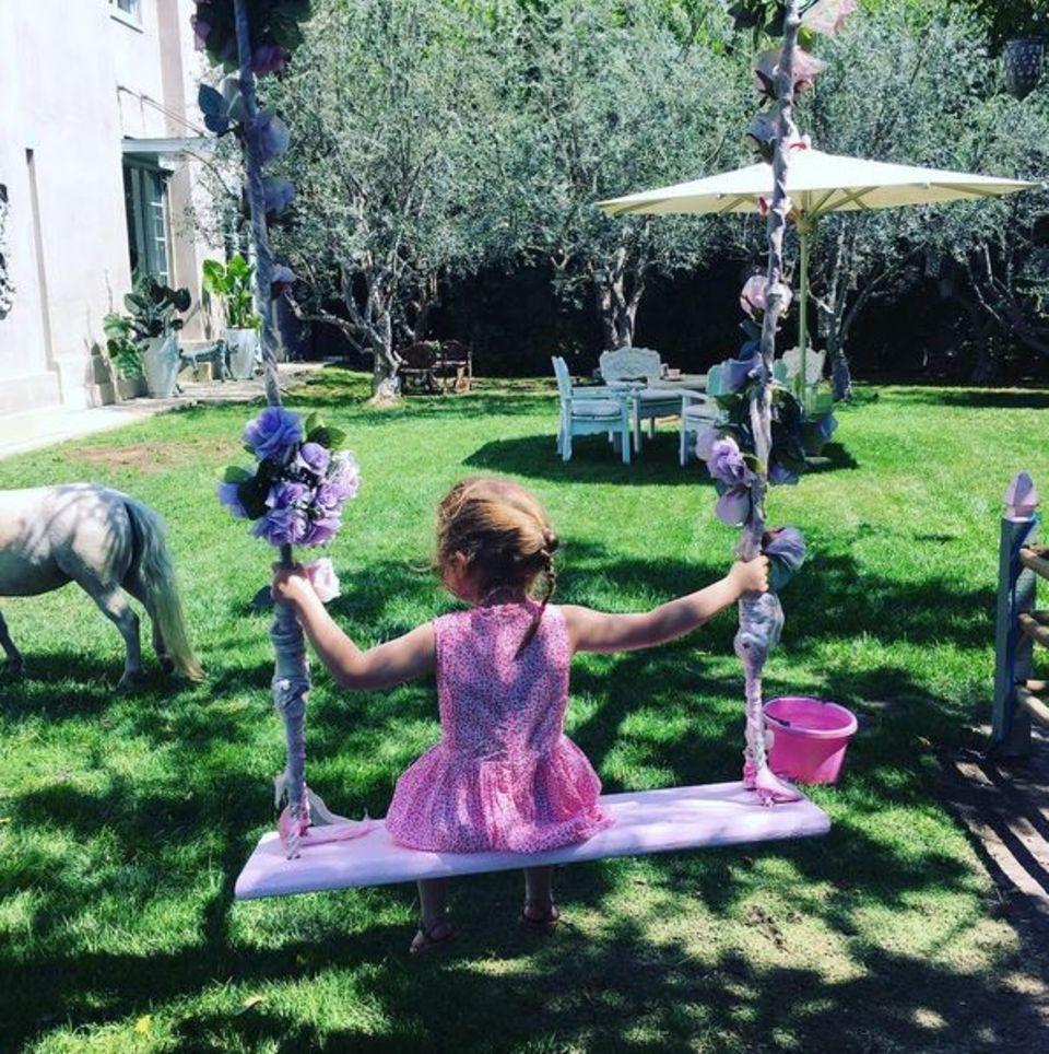 Teddy Rose Williams, die kleine Tochter von Robbie Wiliams und Ayda Field, ist schon so groß! Die Dreijährige schaukelt in einem sommerlichen Kleidchen und könnte von hinten fast als Harper Beckham durchgehen.