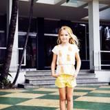 Samantha im weißen Longshirt mit Ananas-Print, von Mini Rodini. Gelbe Shorts von Il Gufo, Ballerinas von Pom d'Api