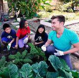 """Lance Bass engagiert sich für die Wohltätigkeitsorganisation """"Environmental Media Association"""", die mit Hilfe der Popularität von Medienstars auf Umweltprobleme aufmerksam machen will. Gemeinsam mit Kindern einer kalifornischen Grundschule bestellt er deren Schulgarten."""
