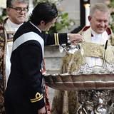 Dem stolzen Onkel Prinz Carl Philip wird die Ehre zuteil, das Taufwasser ins Becken zu gießen.