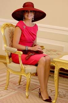 Königin Máxima liebt nicht nur fröhliche Farben, sondern auch opulente Hüte wie diesen rostroten Basthut mit breiter, gebogener Krempe.