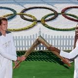 """Die Tennisprofis Andy Murray und Venus Williams halten die Flamme auf dem Tennisplatz des """"All England Lawn Tennis Club""""."""