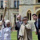 Queen Elizabeth und Prinz Philip verabschieden das olympische Feuer aus Windsor.