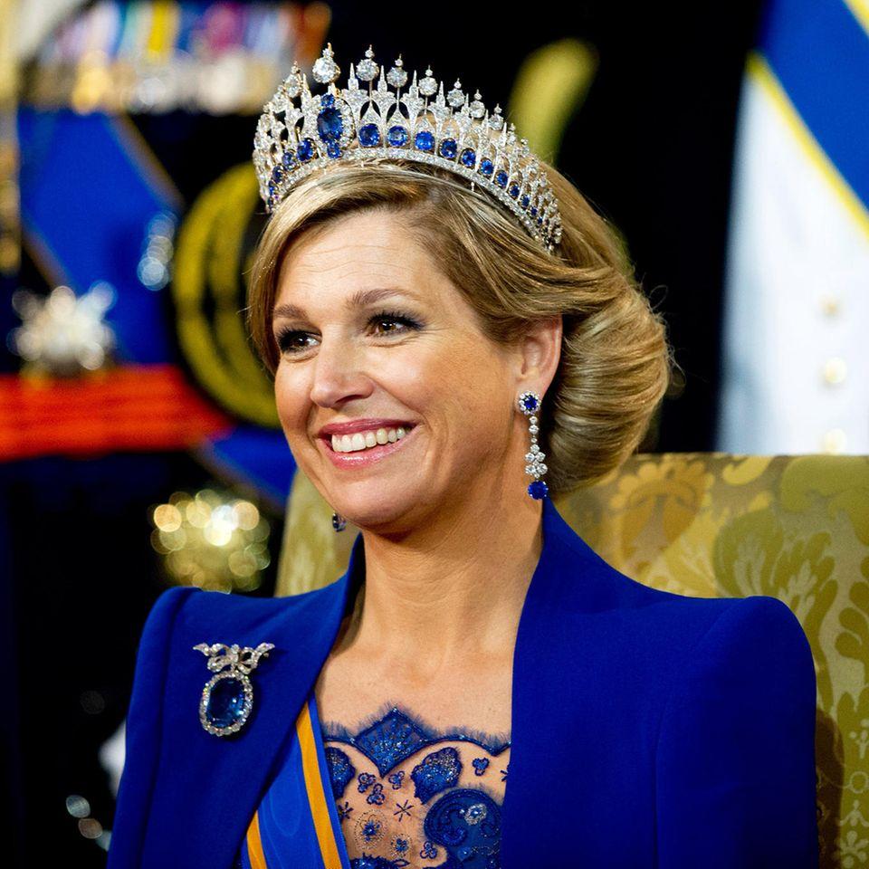 Am Tag ihrer Inthronisierung am 30. April 2013 wechselte Königin Máxima nicht nur mehrfach das Kleid, auch ihren Schmuck und ihre Kopfbedeckung variierte sie. Für die Zeremonie in der Nieuwe Kerk wählte sie eine blaue Robe des Designers Jan Taminiau. Und trug dazu farblich hervorragend passende Stücke aus der königlichen Schmuckschatulle.  Für die Saphir-Tiara mit dazugehöriger Brosche arrangierte der Pariser Juwelier Mellerio 655 Diamanten und 33 Saphire zu einem sehr variablen Schmuckstück, das Königin Emma um 1880 von ihrem Mann König Willem III. bekam.