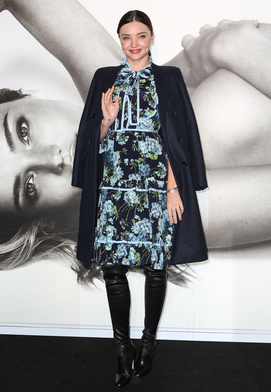 """Bei einem Promotiontermin für ihre Kosmetiklinie """"KORA Organics"""" trägt Miranda Kerr ein geblümtes Kleid. Dazu kombiniert sie schwarze Overknees."""