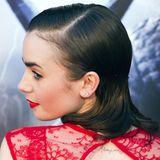 Mit viel Gel und Glanzspray hat Lily Collins ihr braunes Haar in Wasserwellen gelegt.