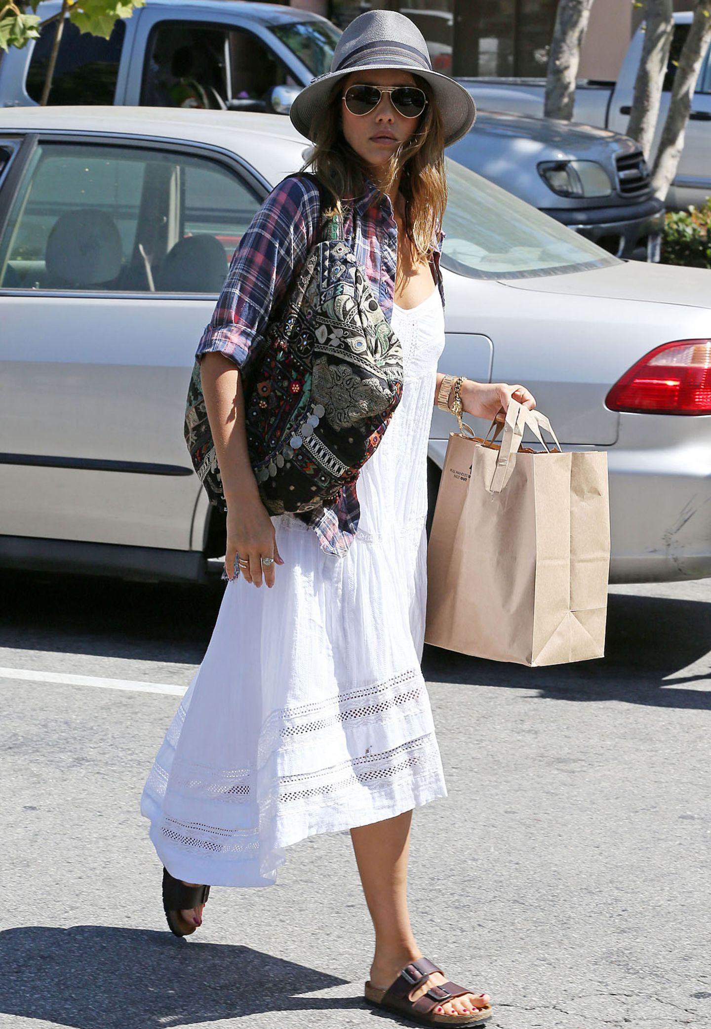 Jessica Alba ist kein Freund von tristen Farben, sondern liebt bunte Muster und farbenfrohe Outfits. Zum weißen Kleid im Western-Stil (ca.250€) trägt die 33-Jährige deshalb ein Cowboy-Hemd (ca.40€) und bringt mit einer bunt gemusterten Tasche im orientalischen Look noch mehr Farbe ins Spiel.