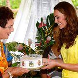 """Kate freut sich über die selbst gebackene Torte, die ihr von den Frauen des """"Commonwealth Youth Programme"""" überreicht wird."""