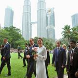 """Vor dem Wahrzeichen Kuala Lumpurs, den Petronas Towers, gehen William und Catherine durch den """"KLCC Park""""."""