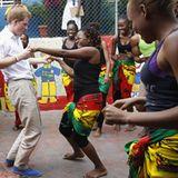 Er kann auch den richtigen Hüftschwung: Bei seinem Besuch in Jamaika zeigt Harry Tänzerinnen in einem Jugendzentrum, wie heißblü