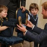 Dieser junge Mann ist ein großer Batman-Fan: Prinz Harry bestaunt seine coolen Batman-Schuhsolen.