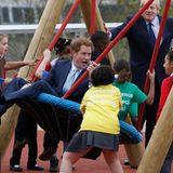 """Prinz Harry und Londons Bürgermeister Boris Johnson weihen einen neuen Spielplatz im """"Queen Elizabeth Olympic Park"""" ein. Während Johnson sich eher im Hintergrund hält, tobt Harry mit den Kindern auf einer Schaukel herum."""
