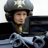 """Prinz Harry besucht gemeinsam mit seiner Mutter Prinzessin Diana die """"Light Dragoons"""". Bei dieser Gelegenheit wird der achtjährige Prinz schon einmal mit einem tarngrünen Helm ausgestattet und kann in einen Panzer klettern."""