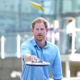 """Dass Prinz Harry wirklich für jeden Klamauk zu haben ist, beweist er mit dieser kuriosen Aktion: In Aberdeen besucht er ein Projekt zur Unterstützung von Jugendlichen und spielt eine Runde """"Toast-Tennis?!""""."""