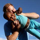 """Prinz Harry lässt den dreijährigen Lerato eine Runde fliegen und wird dabei - mit etwas Hilfe - von einem blinden Mädchen fotografiert. Der Prinz besucht im Dezember 2014 Lesotho, um sich vor Ort von der Arbeit seiner Stiftung """"Sentebale"""" zu überzeugen, die unter anderem für medizinische Versorgung sorgt."""