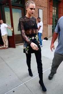 Cara Delevingne trägt ein Oberteil, das ihren BH durchscheinen lässt, dazu einen Minirock und hohe Stiefel. Ein dunkles Augen-Make-up komplettiert ihren coolen Gothic-Look.
