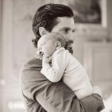 Prinz Carl Philip mit Söhnchen Alexander auf dem Arm. Der kleine Prinz schlummert entspannt auf der Schulter seines Vaters.