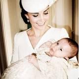 """Herzogin Catherine blickt liebevoll auf ihr Töchterchen Charlotte hinab. Im Hintergrund der """"Drawing Room"""" von """"Sandringham House"""" - in dieser Residenz der Queen fand die Feier nach der Taufe statt."""