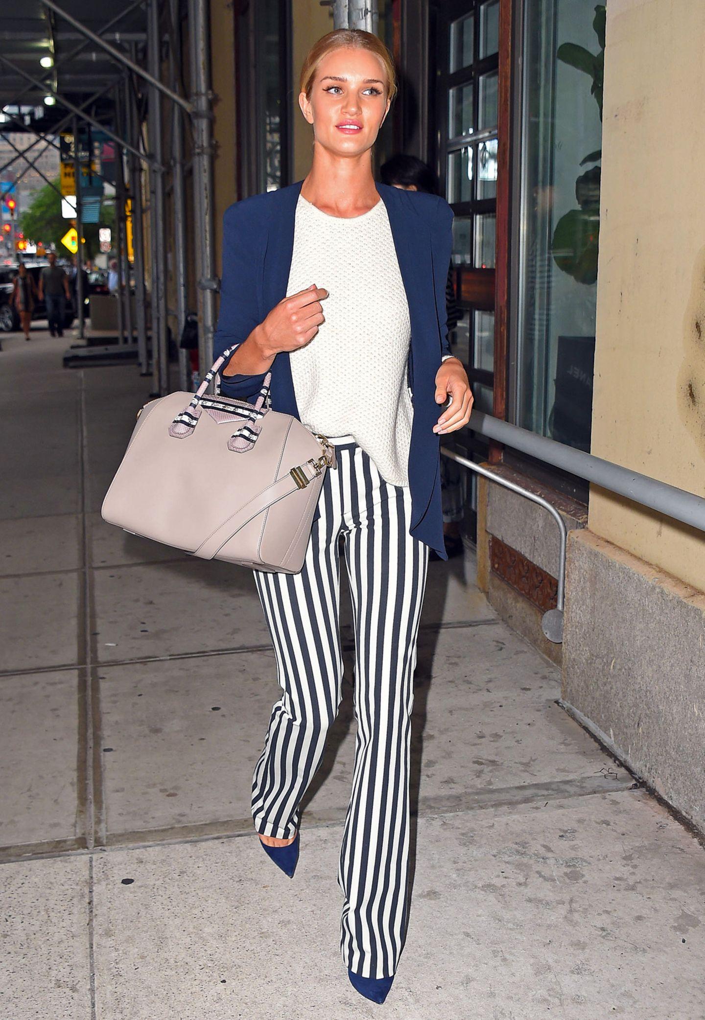 Rosie Huntington-Whiteley hat ihre auffällig längsgestreifte Hose perfekt mit blauer Jacke, weißem Wollshirt und blauen Pumps abgestimmt.
