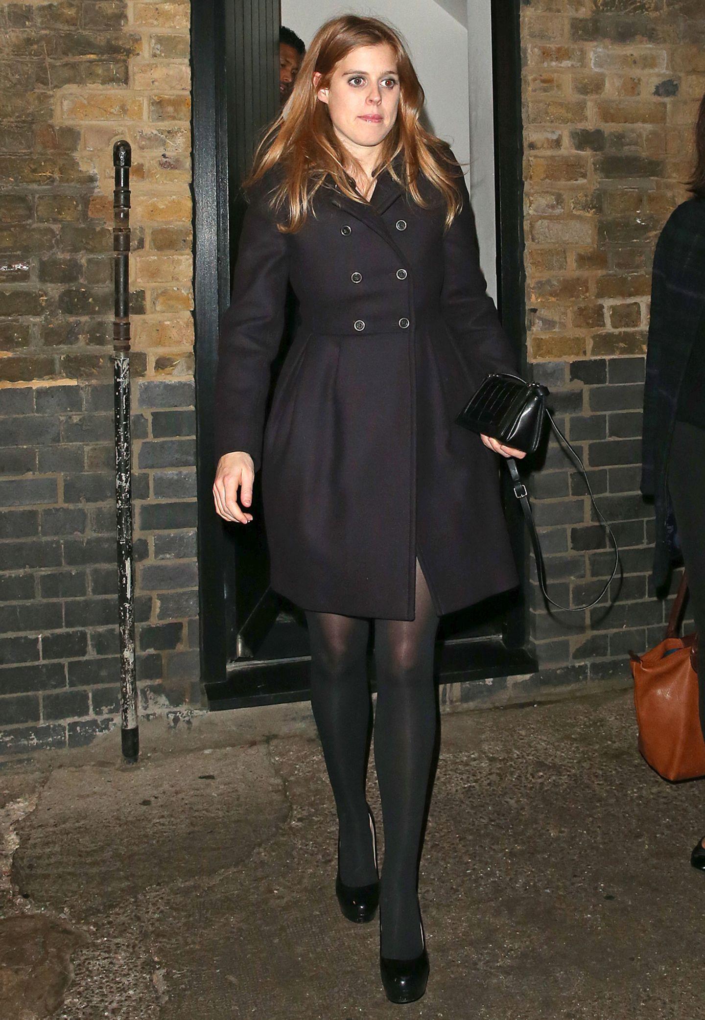Prinzessin Beatrice besucht in elegantem Schwarz ein Londoner Restaurant. Der zweireihige Mantel in A-Linie betont ihre schlanke Silhouette.
