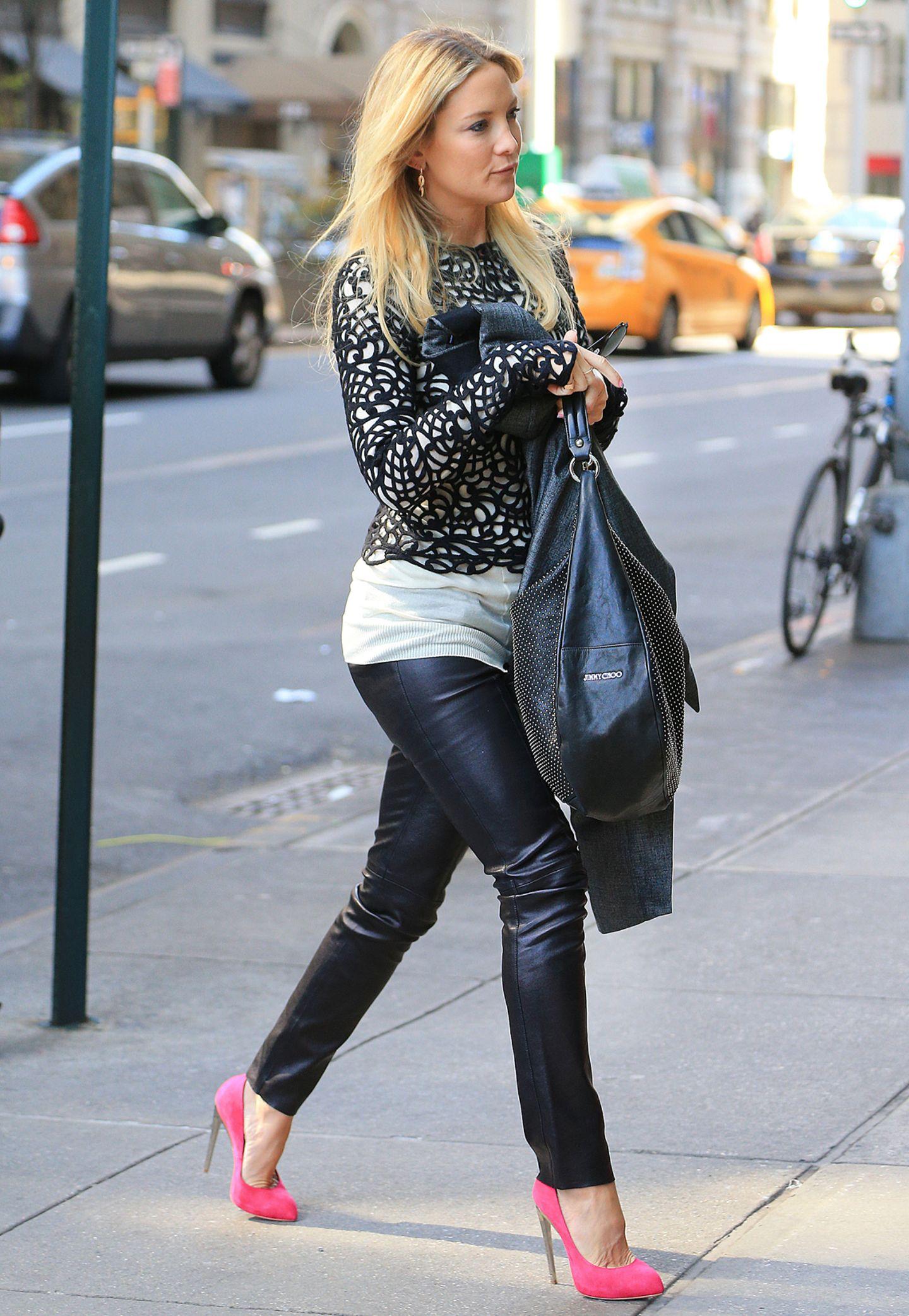 Die sexy Lederhose kombiniert Kate Hudson mit einem ornamentalen Netz-Pulli und pinken High-Heels.