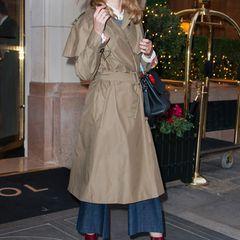 Zum Trenchcoat im Stil von Humphrey Bogart kombiniert Model Natalia Vodianova eine dreiviertellange Schlagjeans und bordeauxrote Stiefeletten aus Lackleder.