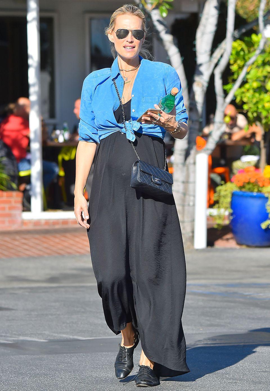 """Wie ein schlichtes, schwarzes Maxikleid innerhalb von Sekunden chic wird, zeigt die schwangere Molly Sims. Sie stylt dazu ein geknotetes Jeans-Hemd und die It-Bag """"2.55"""" von Chanel."""