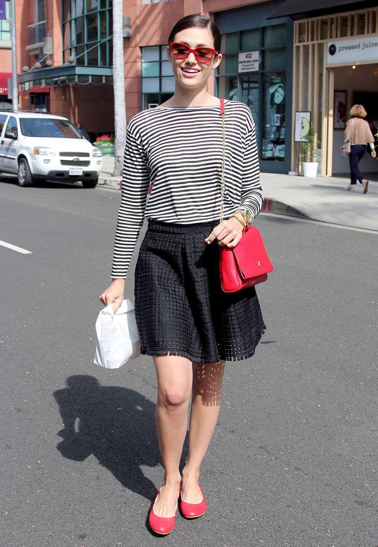 Emmy Rossums schwarz-weißes Streifen-Outfit wird durch die roten Ballerinas, die Handtasche und Sonnebrille perfekt akzentuiert.