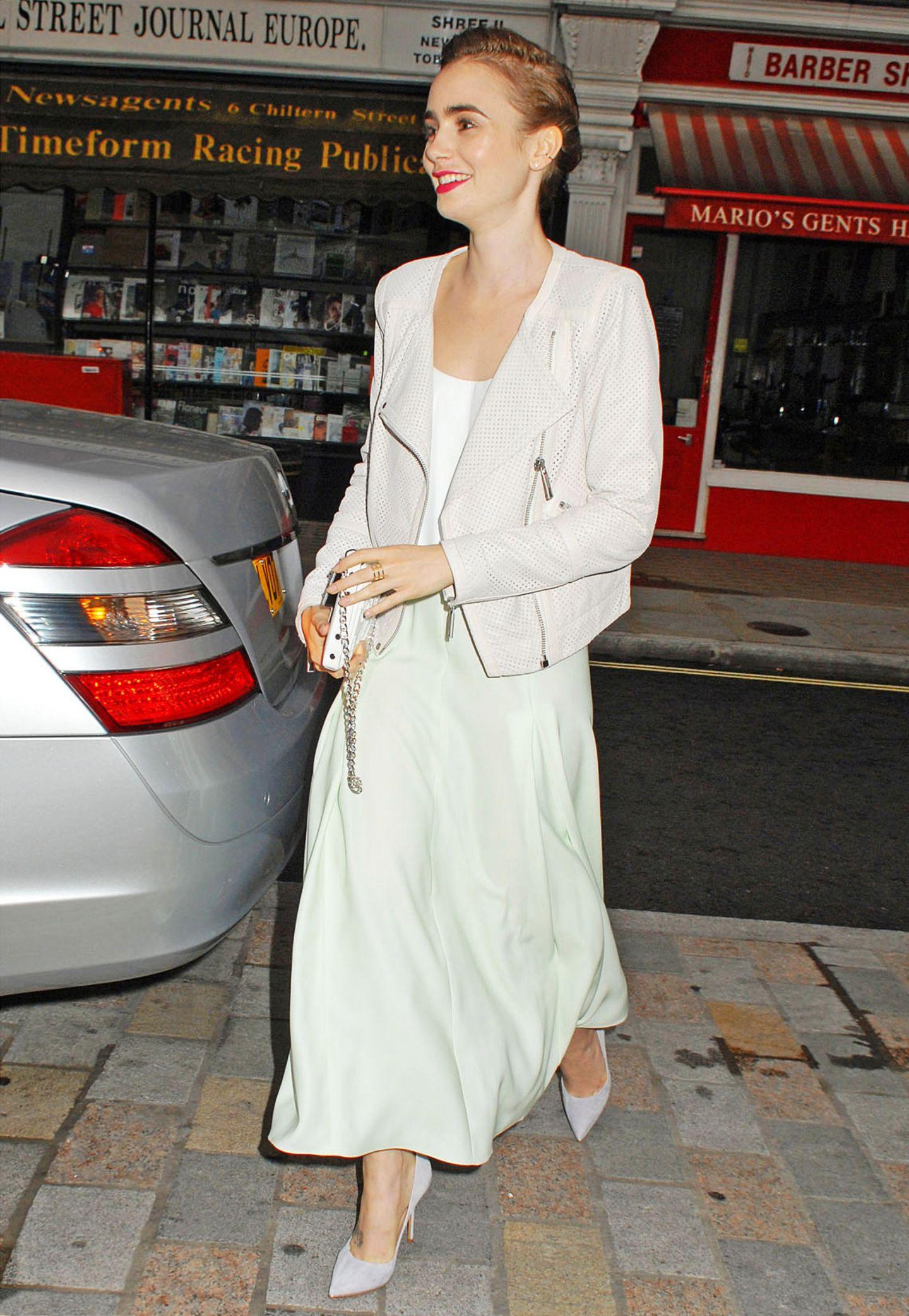 Ihren Ruf als moderne Elfe unterstreicht Lily Collins mit diesem Outfit in zarten Sommerfarben gekonnt. Die weiße Lederjacke mit Lochstanzungen ist ein toller Kontrast zum mintfarbenen Midirock.