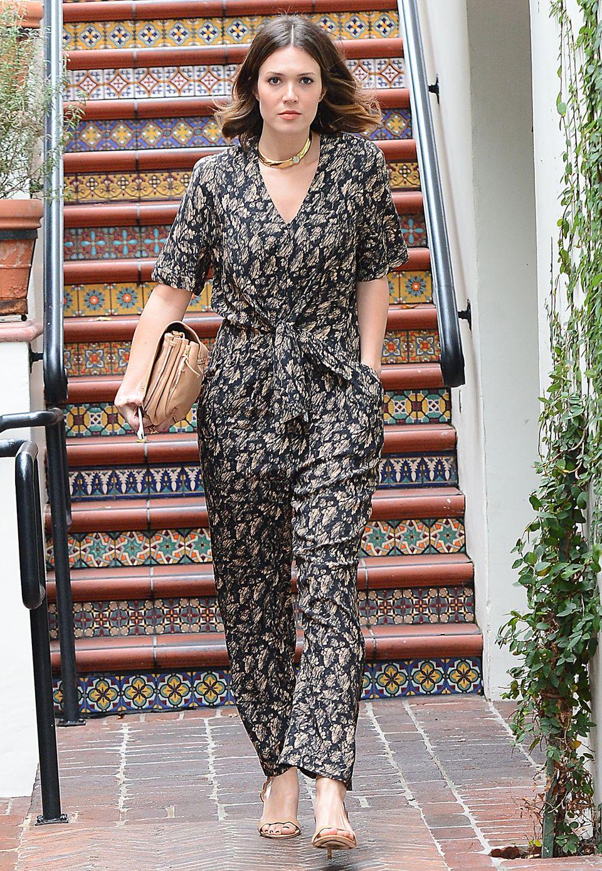 Einem recht legeren Muster-Overall verleiht Mandy Moore mit einer goldenen Statementkette die nötige Portion Eleganz.