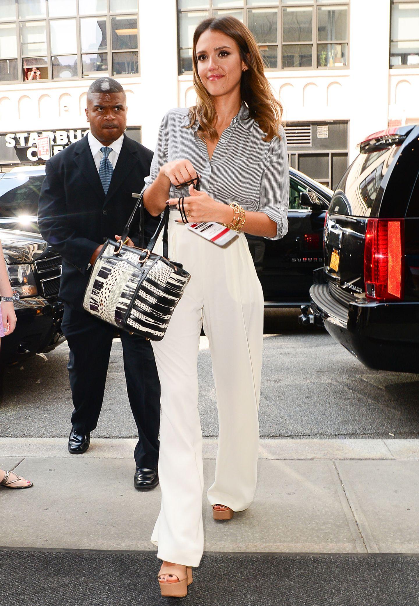 Jessica Alba kombiniert eine cremeweiße Marlenehose zum perfekten Business-Look mit Plateau-Sandaletten und einer gestreiften, weitgeschnittenen Bluse.